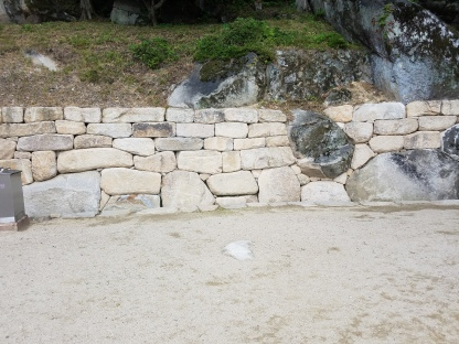 The carved stone wall abuts the mountain